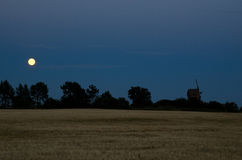 Moon over windmill and a cornfield. In the island Oland in Sweden Royalty Free Stock Image