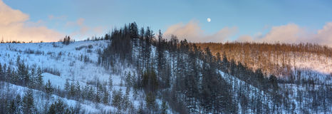 Moon over winter evening hills Royalty Free Stock Photos