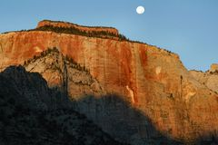 Moon Over Zion. The setting moon over East Temple, captured at sunrise in Zion National Park, Utah Stock Photo