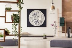 Moon painting above tatami mat bed in japanese style flat interior with ivy on wooden rack and ladder near the window. Real photo stock photos