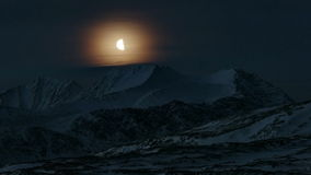 Moon passing over the mountains Royalty Free Stock Photography