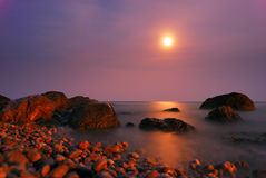 Moon path over the night sea with rocks Stock Image