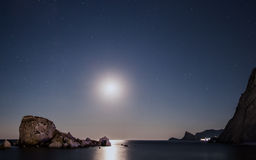 Moon path over the night sea with rocks Royalty Free Stock Photos