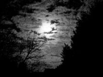 Moon peeking through clouds royalty free stock photos