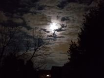 Moon peeking through the clouds stock images
