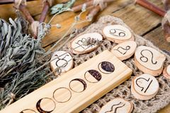 Moon Phases and astrological symbols with herb bundles on rustic wooden background. Moon Phases and astrological symbols with dried herb bundles on rustic wooden royalty free stock images