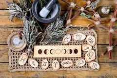Moon Phases and astrological symbols with herb witch mortar and pestle, with branch pentagram and dried herb bundles. On rustic wooden background royalty free stock image