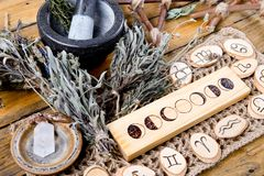 Moon Phases and astrological symbols with herb witch mortar and pestle, with branch pentagram and dried herb bundles. On rustic wooden background stock photo