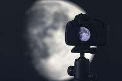 Moon photography. Camera with tripod capturing moon. Royalty Free Stock Images
