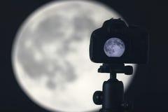 Moon photography. Camera with tripod capturing moon. Royalty Free Stock Photos