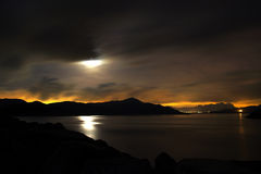 Moon and pond in a cloudy night. With the city lights that dyed the far sky into orange. Shot at High Island Reservoir East dam, sai kung, Hong Kong royalty free stock photo