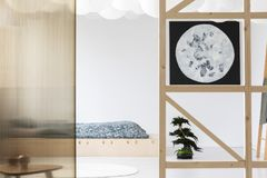 Moon poster on white wall in japanese bedroom interior. With sheets on wooden bed. Real photo stock image