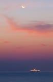 Moon prima sopra il mare e la nave da guerra Fotografia Stock