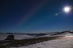 The moon with the rays and the northern lights in Iceland s blue winter sky over an Icelandic house that stands on a lava field royalty free stock photos