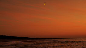 Moon and red sky at sunset. Moon rise over sea and red sky after sunset royalty free stock photo