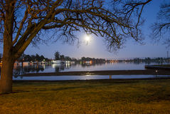 Moon reflected on a lake. Full moon low in the sky reflected on a lake Royalty Free Stock Images