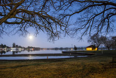 Moon reflected on a lake. Full moon low in the sky reflected on a lake Royalty Free Stock Photography