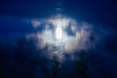 Moon reflecting in misty water surface Stock Image