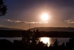 Moon Reflects off Abiquiu Lake under Night Sky. The full moon reflects off the clouds and water of Abiquiu Lake in northern New Mexico stock image