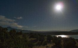 Moon Reflects off Abiquiu Lake under Night Sky. The full moon reflects off the water of Abiquiu Lake in northern New Mexico royalty free stock image
