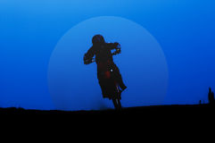 Moon rider. A motocross rider under perfect blue sky in the evening Stock Photo