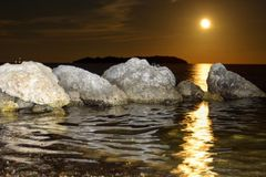 Moon rise reflecting on the water with rocks and island Royalty Free Stock Image