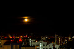 The moon rises above the lights of the night city. Time Lapse. The moon rises above the lights of the night city Stock Photos