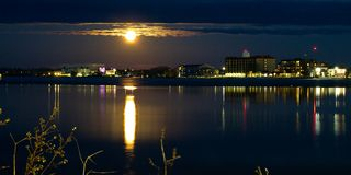 Moon rises over buildings and reflects in Lake Bemidji in Minnesota. Moon and clouds over buildings reflects in a partially frozen Lake Bemidji in Minnesota on a royalty free stock photography