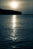 The moon rises over the ocean at night Royalty Free Stock Image