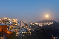 The moon rises over Oia. On Santorini island, Greece Royalty Free Stock Image