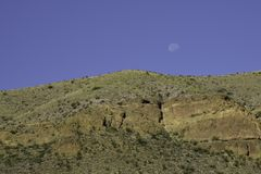 Moon rising over the hill. Moon rising in a bright blue cloudless sky over the hill stock image