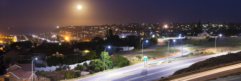 Moon rising. A large moon rising over the town of Mossel Bay. It was a supermoon. There are large homes built on the hillside Royalty Free Stock Photo