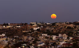 Moon rising over coastal town and homes, super moo. A large moon rising over the town of Mossel Bay. It was a supermoon. There are large homes built on the Royalty Free Stock Photo