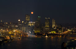 Moon rising over downtown Royalty Free Stock Images