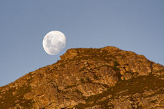 Moon rising over mountain. Scenic view of moon rising over top of rocky mountain Stock Image