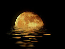 Moon rising over the sea. Golden moon rising over the sea with a rippled reflection Royalty Free Stock Photos