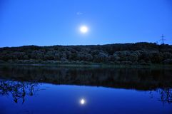 Blue wather under moon. Moon and river for a summer night royalty free stock images