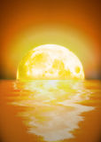 Moon Set. A setting or rising full moon reflecting on water Royalty Free Stock Photography