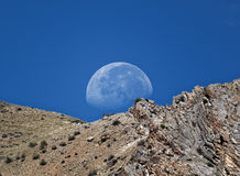 The moon setting behind the mountain looks amazing. Royalty Free Stock Images