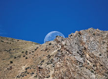 The moon setting behind the mountain looks amazing. The moon is beautifully hiding behind the mountain Royalty Free Stock Image