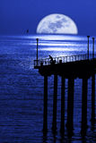 Moon setting. Over ocean and pier Royalty Free Stock Photos