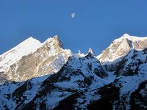 Moon shining atop mountains in daytime Royalty Free Stock Image