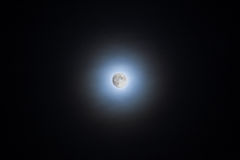 Moon shining through clouds making a halo Royalty Free Stock Images