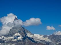 Moon shining over the famous matterhorn with clouds and blue sky royalty free stock photography
