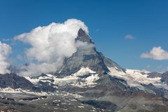 Moon shining over the famous matterhorn with clouds and blue sky Stock Image