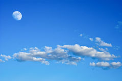 Moon in the sky. Moon in the blue sky with clouds Royalty Free Stock Photo