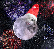 The moon smiles in  New Year's cap against salute Stock Photos