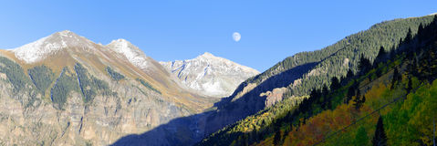 Moon, snow covered mountains and yellow aspen Royalty Free Stock Image
