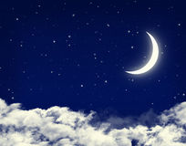 Moon and stars in a cloudy night blue sky Royalty Free Stock Photos