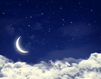 Moon and stars in a cloudy night blue sky. Background Stock Images